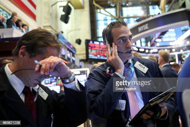 Traders and financial professionals work ahead of the closing bell on the floor of the New York Stock Exchange June 25 2018 in New York City The Dow...