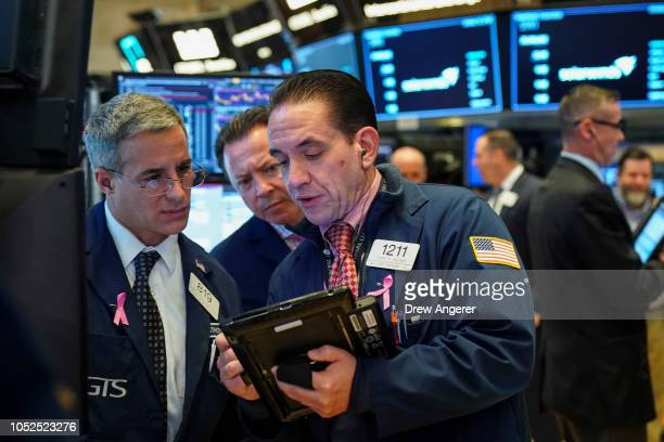 Traders and financial professionals work ahead of the opening bell on the floor of the New York Stock Exchange October 19 2018 in New York City US...