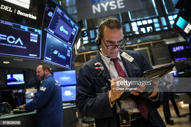 Traders and financial professionals work ahead of the opening bell on the floor of the New York Stock Exchange June 19 2018 in New York City US...