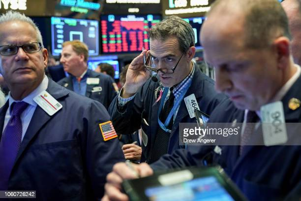Traders and financial professionals work at the closing bell on the floor of the New York Stock Exchange November 12 2018 in New York City The Dow...