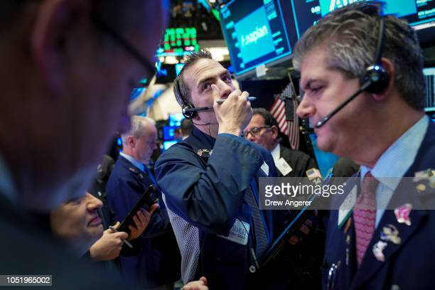 Traders and financial professionals work at the opening bell on the floor of the New York Stock Exchange October 12 2018 in New York City The Dow...