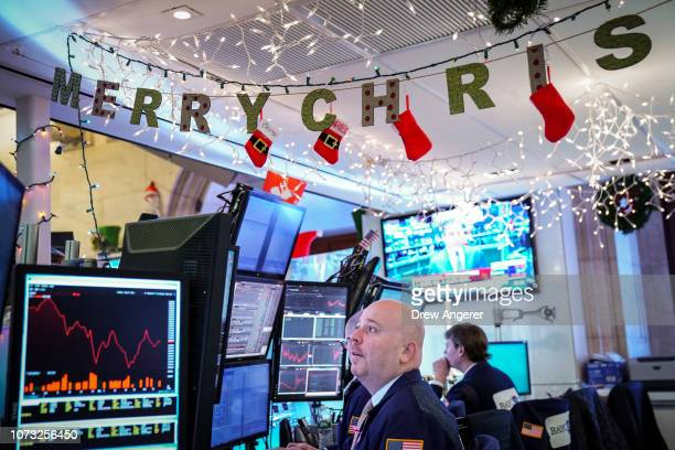 Traders and financial professionals work at the opening bell on the floor of the New York Stock Exchange December 14 2018 in New York City The Dow...
