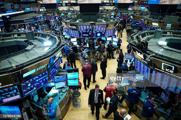 Traders and financial professionals work at the opening bell on the floor of the New York Stock Exchange January 2 2019 in New York City The Dow...