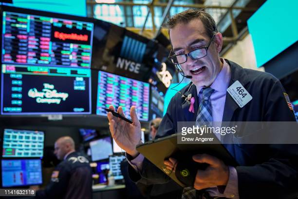 Traders and financial professionals work at the opening bell on the floor of the New York Stock Exchange , May 6, 2019 in New York City. The Dow...
