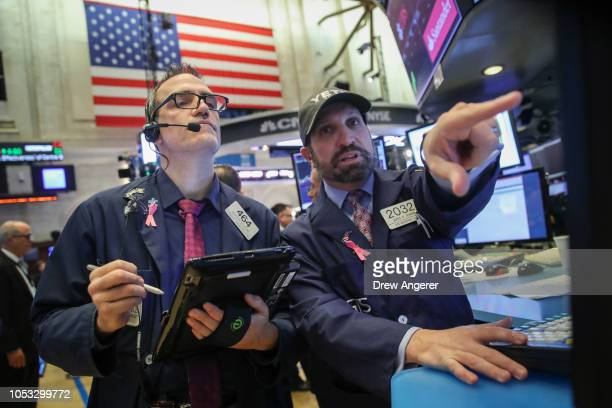 Traders and financial professionals work on the floor of the New York Stock Exchange at the opening bell, October 25, 2018 in New York City....