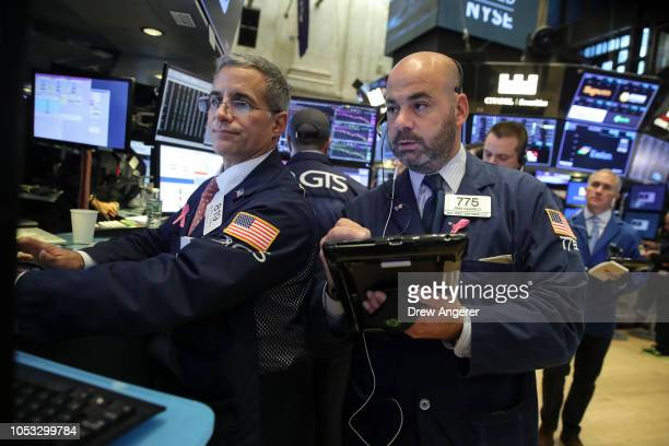 Traders and financial professionals work on the floor of the New York Stock Exchange at the opening bell October 25 2018 in New York City Following a...