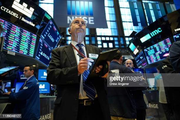 Traders and financial professionals work on the floor of the New York Stock Exchange at the opening bell April 24 2019 in New York City US stocks...