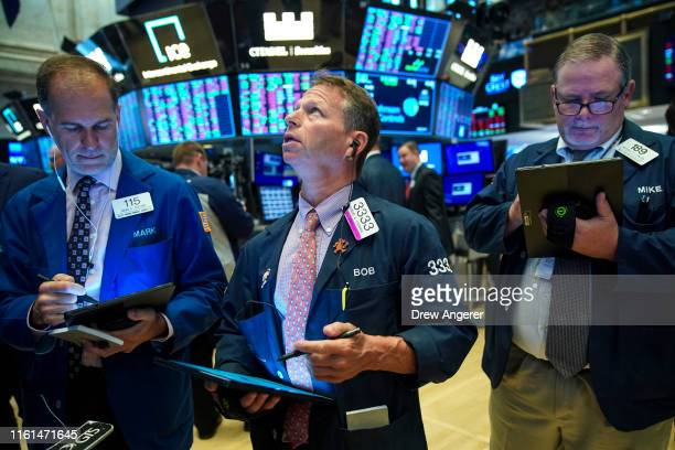Traders and financial professionals work on the floor of the New York Stock Exchange at the opening bell on August 13 2019 in New York City The Dow...
