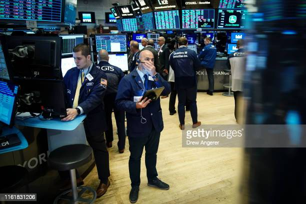 Traders and financial professionals work on the floor of the New York Stock Exchange at the opening bell on August 15, 2019 in New York City....