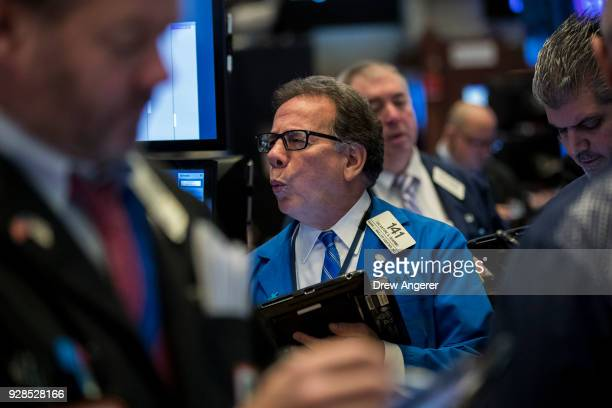 Traders and financial professionals work on the floor of the New York Stock Exchange ahead of the opening bell March 7 2018 in New York City US...