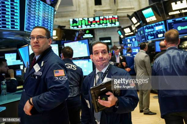 Traders and financial professionals work on the floor of the New York Stock Exchange ahead of the opening bell April 4 2018 in New York City The Dow...