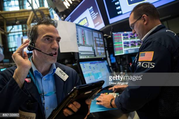 Traders and financial professionals work the floor of the New York Stock Exchange ahead of the opening bell, August 11, 2017 in New York City. After...