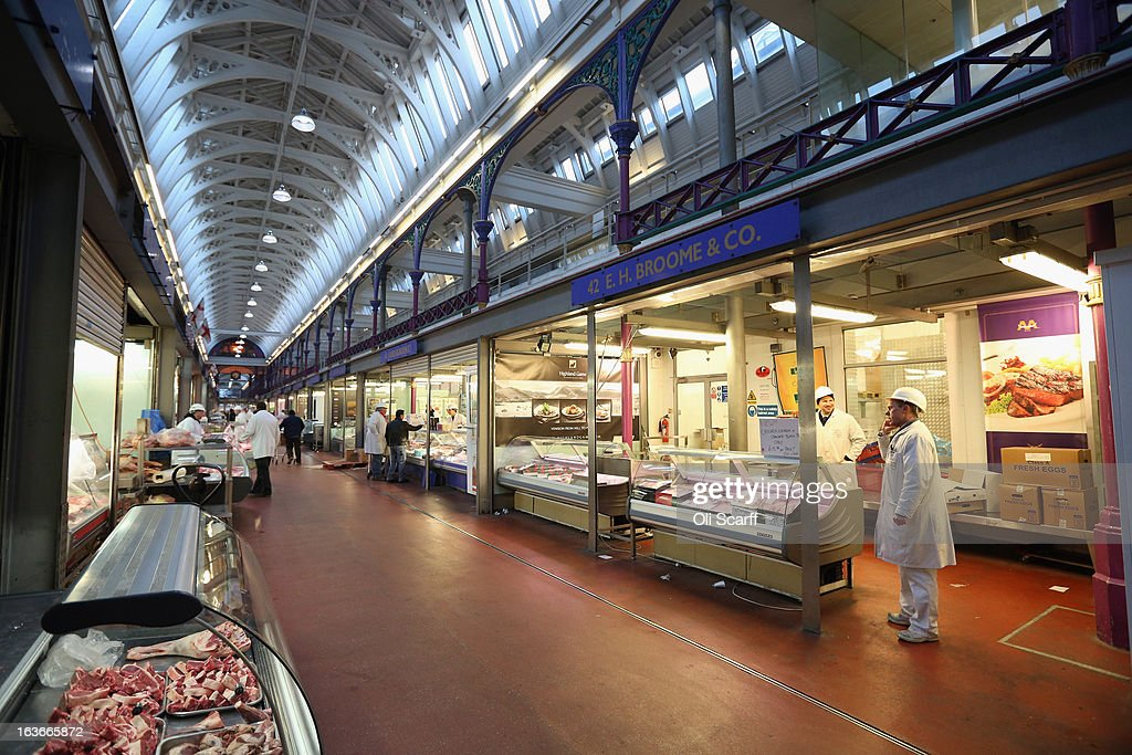 Traders and shoppers walk past butchers stalls in Smithfield Market on March 14, 2013 in London, England. Smithfield Market, which is officially named the 'London Central Markets', has been the site of a livestock market since the Twelfth Century. Located in the City of London, the market's Victorian buildings were designed by Sir Horace Jones, the City Architect, and were completed in the 1860s. Developers have recently proposed a 160 million GBP refurbishment of the derelict western end of Smithfield Market into an artisan food centre known as 'Smithfield Quarter'.