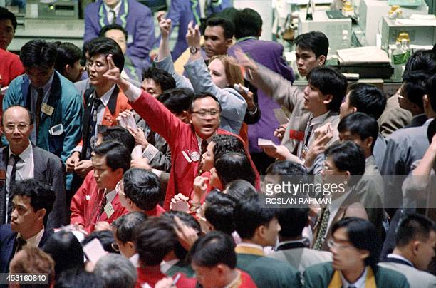 Traders at the Singapore International Monetary Exchange make signs during the afternoon trading on February 27 1995 on the Nikkei 225 Index trading...