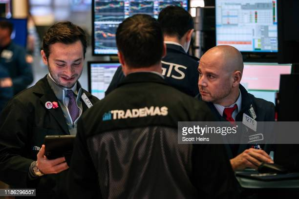 Traders check stock prices on the floor of the New York Stock Exchange on December 3, 2019 in New York City. The Dow Jones Industrial Average dipped...
