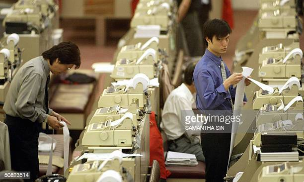 Traders check their printouts at the end of trading at the Hong Stock Stock Exchange, 11 May 2004, as the Hang Seng Index recovers from earlier...