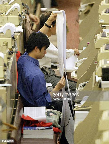 Traders checks a printout at the end of trading at the Hong Stock Stock Exchange, 11 May 2004, as the Hang Seng Index recovers from earlier losses to...