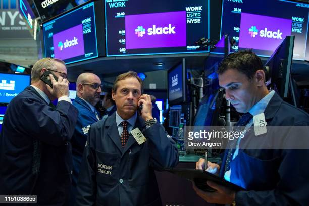 Traders gather around a post as they wait for shares of Slack to start trading at the New York Stock Exchange , June 20, 2019 in New York City. The...