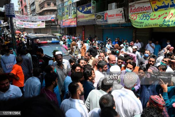 Traders gather as they protest beside their closed shops against a lockdown imposed by the Punjab provincial government in an effort to curb the...