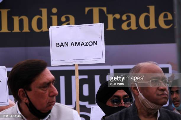 Traders hold placards and shout slogans during a sit-in protest in support of a nationwide strike called by the Confederation of All India Traders...