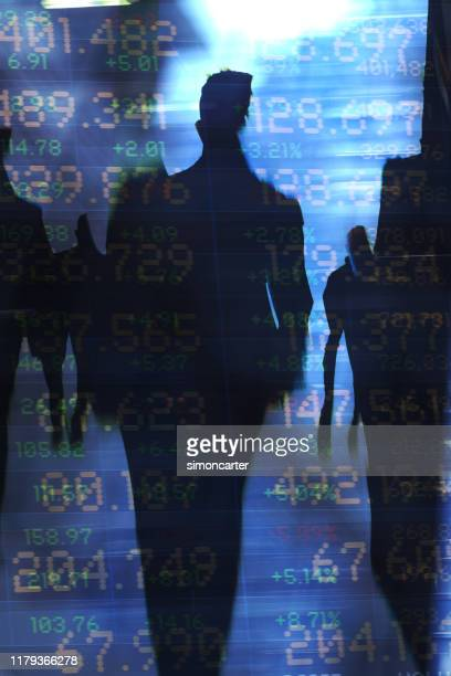 traders in financial district with trading screen data. - wealth stock pictures, royalty-free photos & images