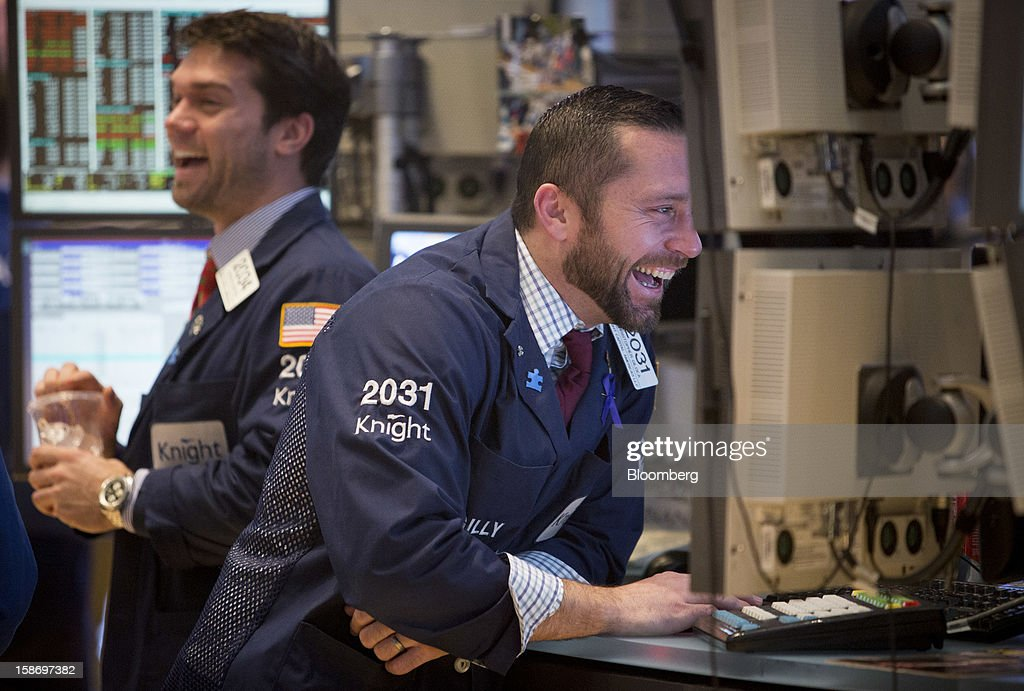 Traders laugh as they work on the floor of the New York Stock Exchange (NYSE) in New York, U.S., on Monday, Dec. 24, 2012. Americans have missed out on almost $200 billion of stock gains as they drained money from the market in the past four years, haunted by the financial crisis. Photographer: Scott Eells/Bloomberg via Getty Images