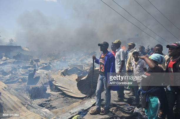 Traders look on at smouldering remains after open air stalls used in selling secondhand clothing burned down in a fire that gutted capital Nairobi's...