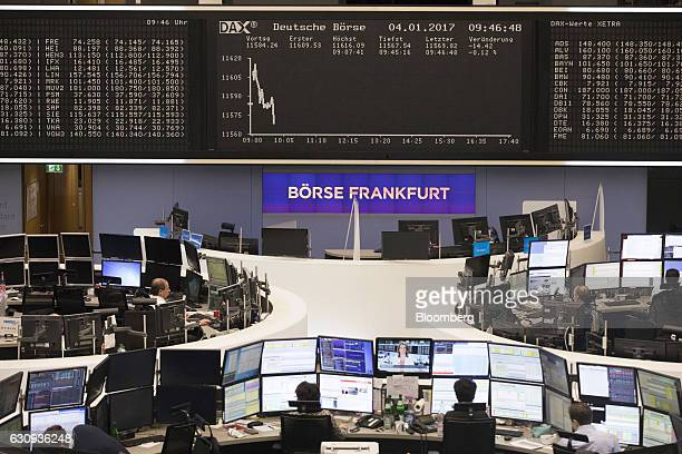 Traders monitor financial data as the DAX Index curve is displayed beyond inside the Frankfurt Stock Exchange in Frankfurt Germany on Wednesday Jan 4...