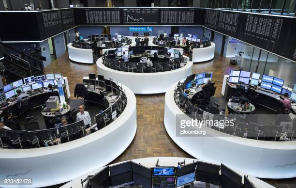 Traders monitor financial data as the DAX index curve shows stock information inside the Frankfurt Stock Exchange operated by Deutsche Boerse AG in...