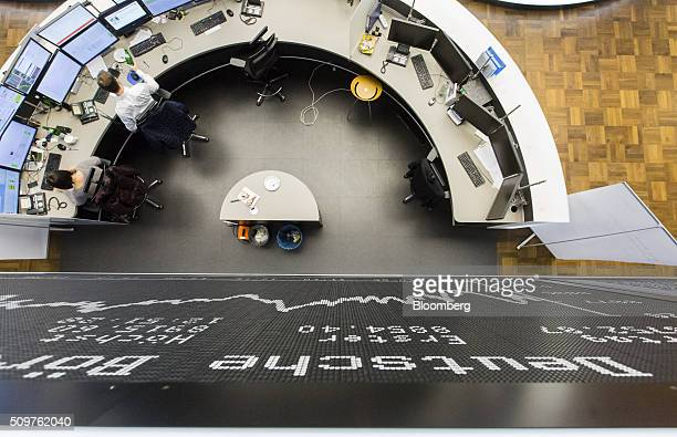 Traders monitor financial data as the DAX Index curve sits displayed on an electronic board inside the Frankfurt stock exchange in Frankfurt Germany...