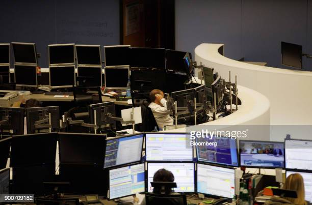 Traders monitor financial data as the second iteration of the Markets in Financial Instruments Directive comes into force at the Frankfurt Stock...