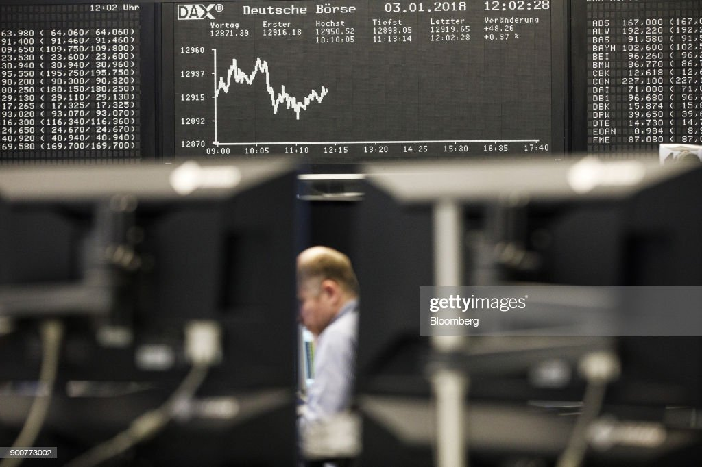 Traders monitor financial data as the second iteration of the Markets in Financial Instruments Directive (MiFID II) comes into force, as the DAX Index curve is displayed beyond at the Frankfurt Stock Exchange, operated by Deutsche Boerse AG, in Frankfurt, Germany, on Wednesday, Jan. 3, 2018. After seven years of preparation, $2 billion in compliance costs and one false start, the biggest shake-up to European regulation in a decade is finally here. Photographer: Alex Kraus/Bloomberg via Getty Images
