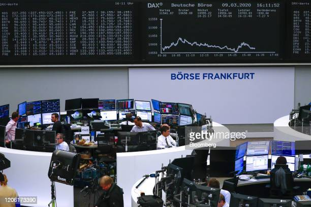 Traders monitor financial data near the DAX Index curve inside the Frankfurt Stock Exchange, operated by Deutsche Boerse AG, in Frankfurt, Germany,...