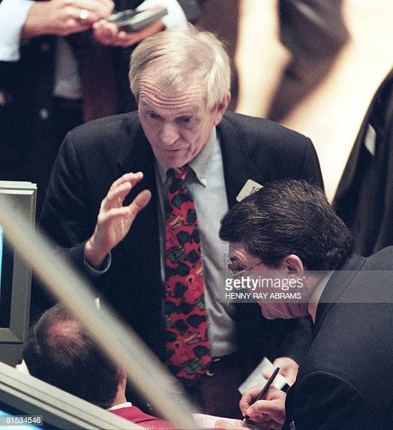 Traders on the floor of the New York Stock Exchange gather around the monitors late on a trading day as the Dow Jones Industrial Average soared to a...