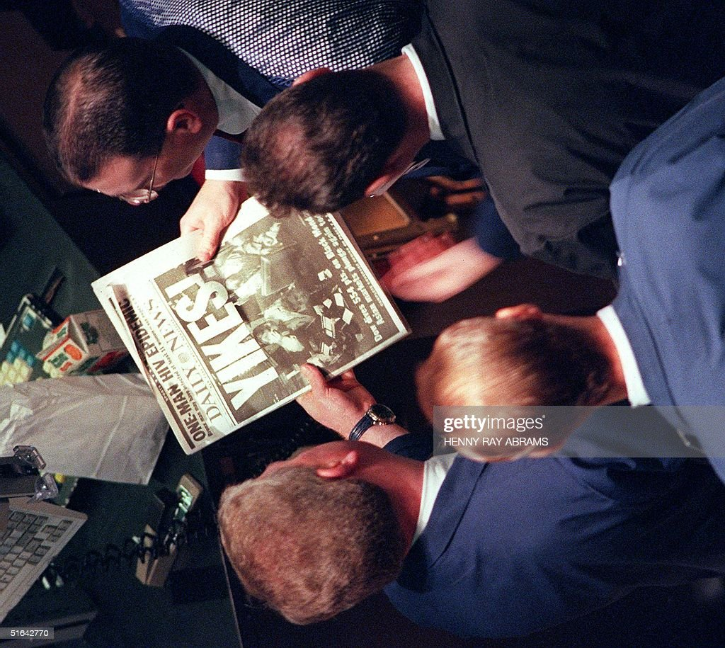 Traders on the floor of the New York Stock Exchange look at a copy of the New York Daily News 28 October which shows the headline 'Yikes.' Stocks began a recovery early and the Dow Jones index was up 117 points shortly after 11 am. AFP PHOTO/Henny Ray ABRAMS