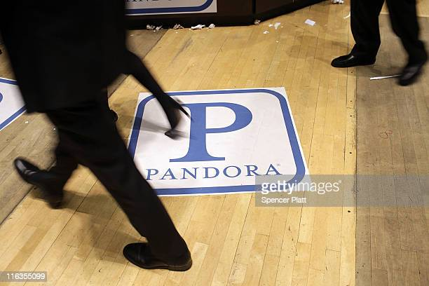 Traders on the floor of the New York Stock Exchange walk over insignia for Pandora Media Inc the onlineradio company on its first day of trading as a...