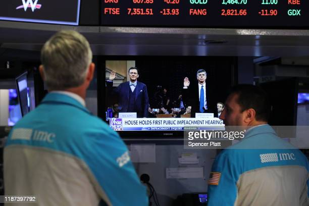 Traders on the floor of the New York Stock Exchange watch the opening of the public hearing in the impeachment inquiry of President Donald Trump on...