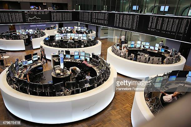 Traders on the trading floor of the Frankfurt Stock Exchange as a graph shows the day's performance of the DAX index the day after the 'NO' vote in...