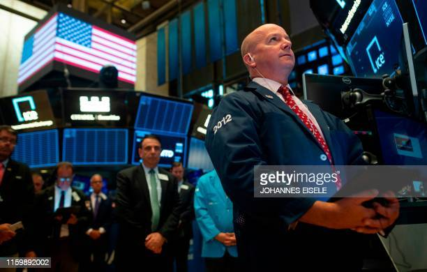 Traders pause in a minute of silent to remember the two mass shooting in America before the opening bell at the New York Stock Exchange on August 5...