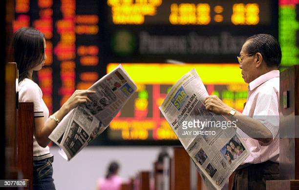 Traders read news papers about the bomb blast in Spain at the trading floor of the Philippines Stock Exchange in Manila 12 March 2004 Philippine...