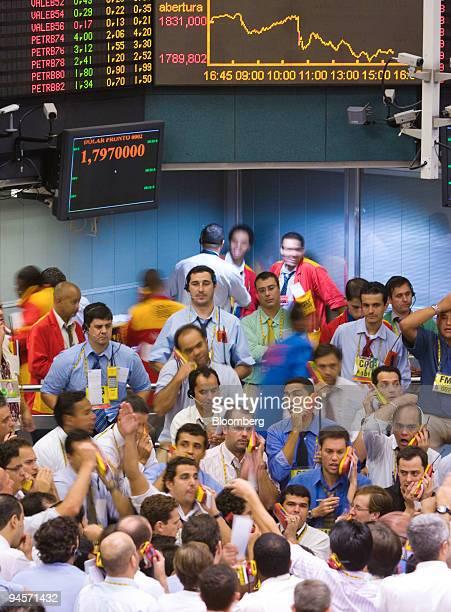 Traders signal at the Brazilian Bolsa de Mercadorias e Futuros or Brazilian Mercantile and Futures Exchange in Sao Paulo Brazil on Tuesday Jan 22...