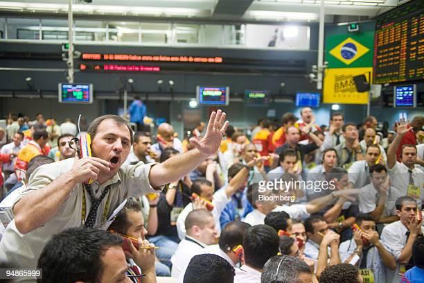 Traders signal at the Brazilian Bolsa de Mercadorias e Futuros or Brazilian Mercantile and Futures Exchange in Sao Paulo Brazil on Friday April 4...