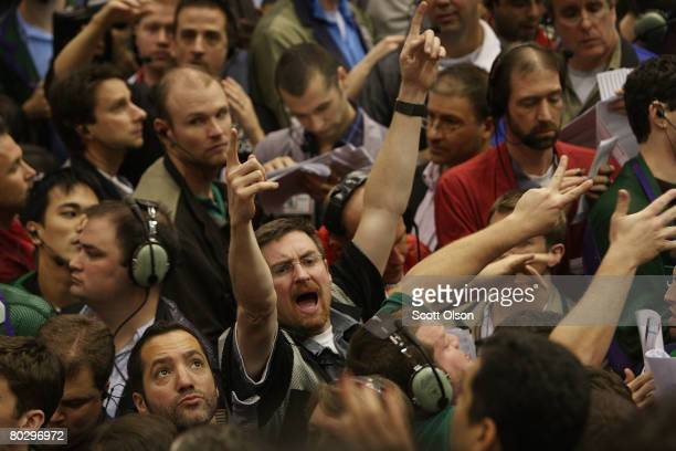 Traders signal offers in the Eurodollar options pit at the Chicago Mercantile Exchange following the announcement from the Federal Open Market...