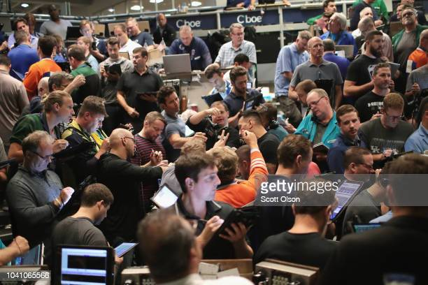 Traders signal offers in the SP options pit at the Cboe Global Markets exchange shortly after the Federal Reserve announced it was raising interest...
