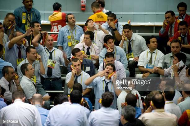 Traders signal orders at the Brazilian Bolsa de Mercadorias e Futuros or Brazilian Mercantile and Futures Exchange in Sao Paulo Brazil on Thursday...