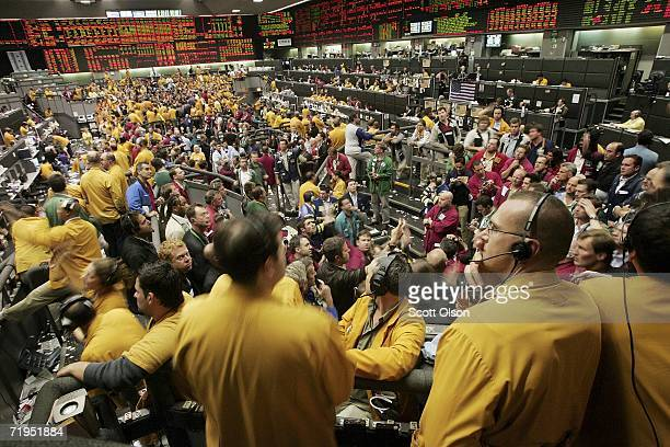 Traders signal prices and offers from the Eurodollar options pit at the Chicago Mercantile Exchange following the announcement from the Federal Open...