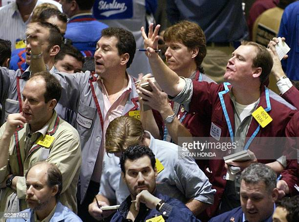 Traders signal with their hands and yell for attention in the oil futures pit 07 March 2005 at the New York Mercantile Exchange During the past two...
