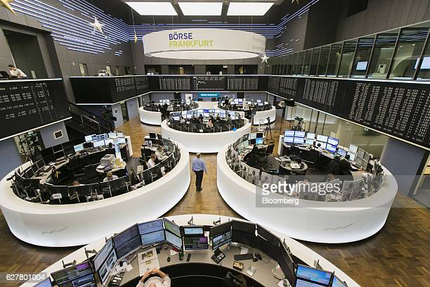 Traders sit at desks and monitor financial data underneath the DAX Index curve displayed on screen inside the Frankfurt Stock Exchange in Frankfurt...