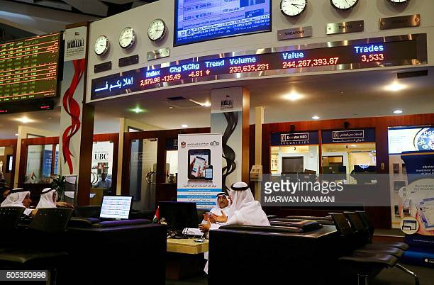 Traders sit at the Dubai bourse as prices of shares are reflected on screens in red above them on January 17 2016 Share prices in the energyrich Gulf...