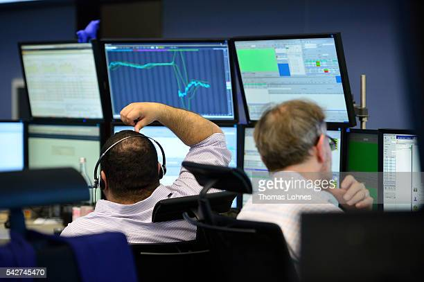 Traders sit at their desk at the Frankfurt Stock exchange the day after a majority of the British public voted for leaving the European Union on June...